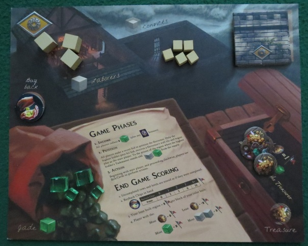 This is a photo of a player mat with three laborers, five convicts, two wall blocks, one buyback token, four jade cubes totaling eight jade currency points, and four treasures on it.
